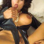 girl in leather licking her big breasts and shoving very big dildo up into her pussy
